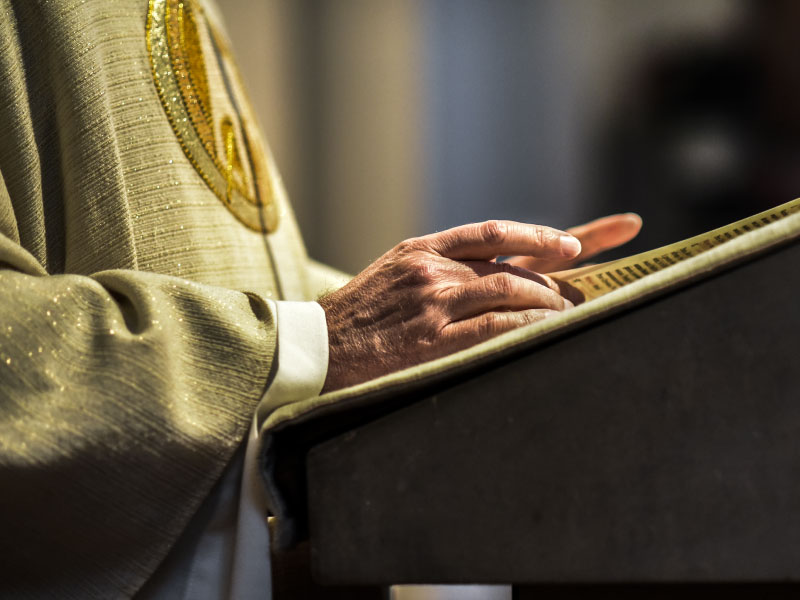 Priest preaching from a lectern image